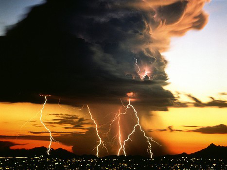 Photo of electric storm over a city with mountains behind